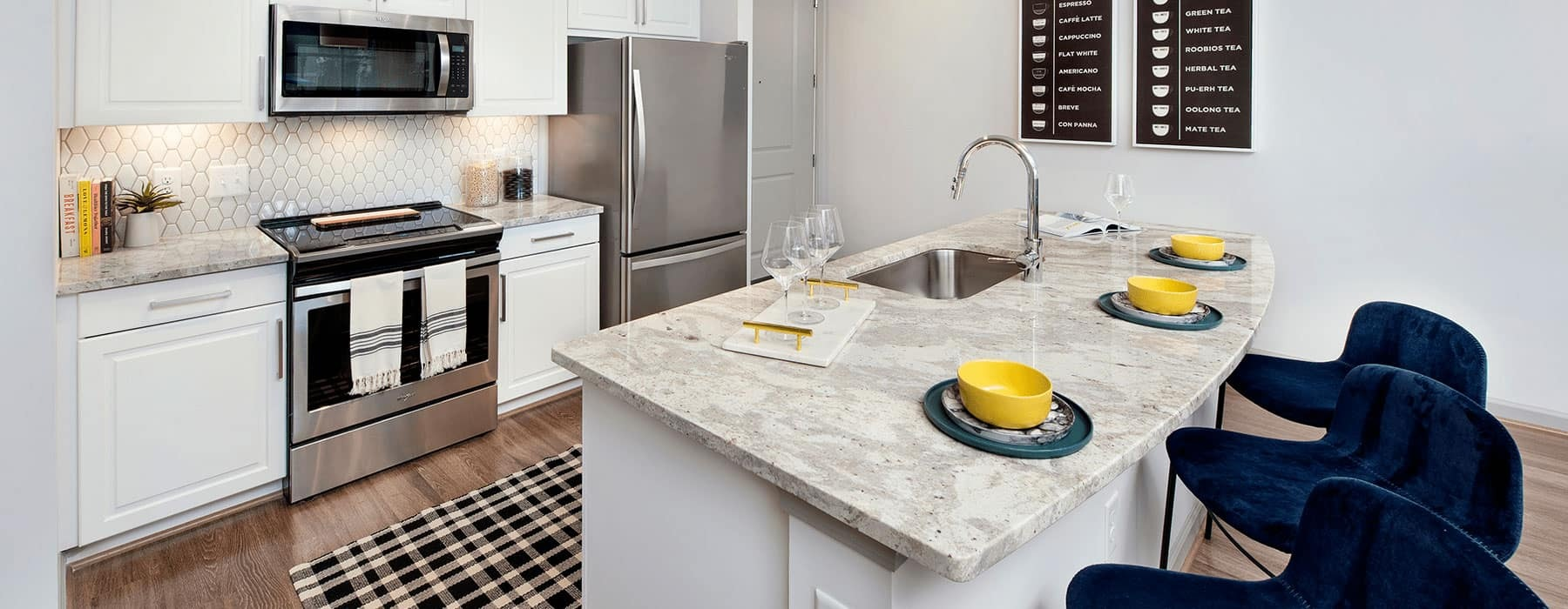 spacious kitchen with an island, ample counter-space & on wood-style flooring