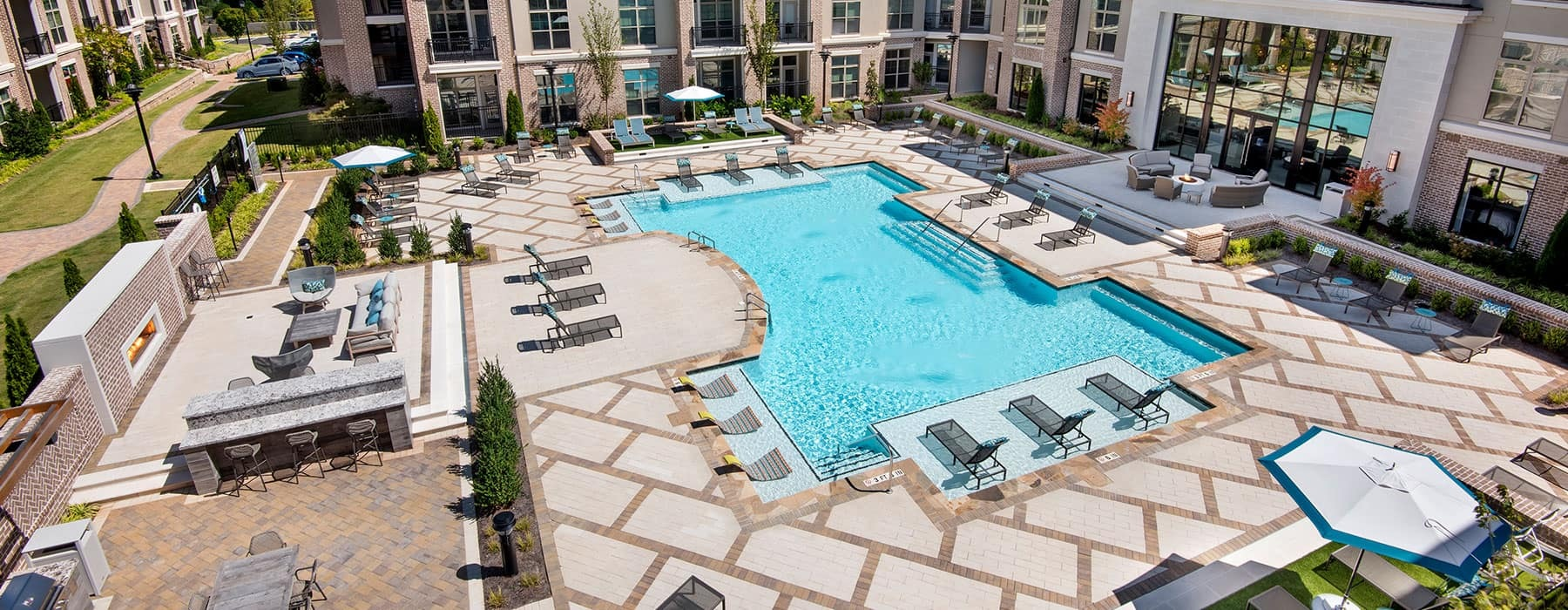 aerial view of swimming pool with modern tile-work and ample seating