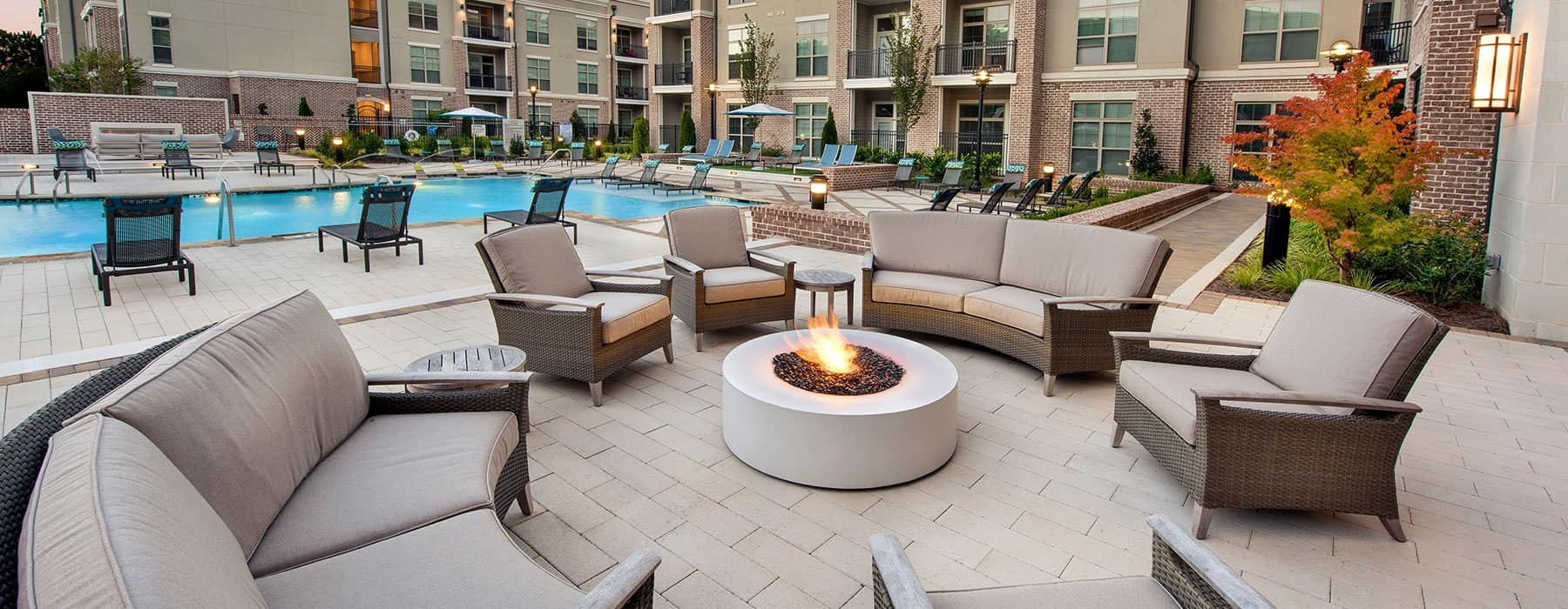 spacious seating surrounding a small firepit and near to the swimming pool